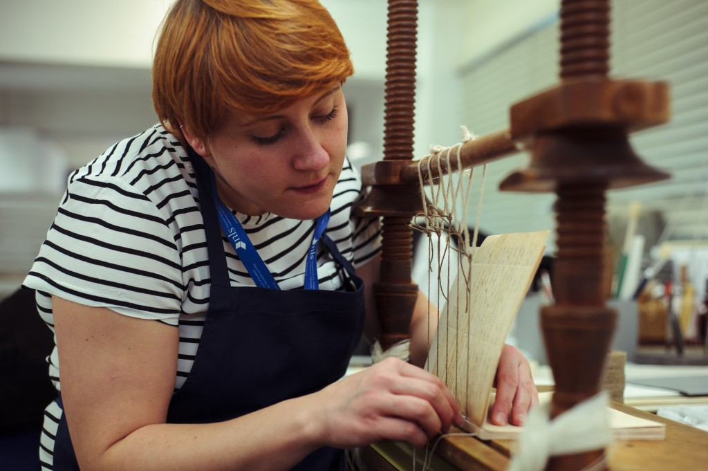 Figure 2 Sarah Wilmott, Conservation Technician, sewing a book using a sewing frame, Courtesy of The National Library of Scotland, March 2016, Maverick Photography.
